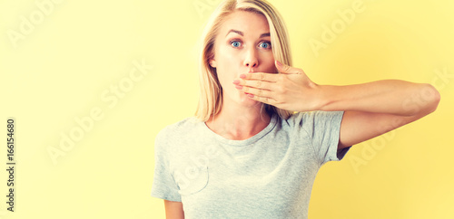 Fototapeta Young woman covering her mouth on a yellow background