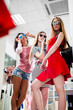 Women trying new ladies summer collection of clothes and accessories looking in mirror in clothing store