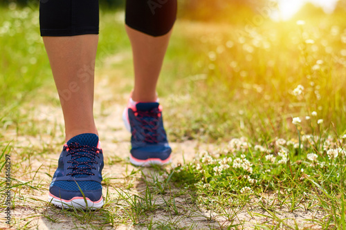 Girl is engaged in cardio runs through forest in sneakers, only legs are visible, legs and sneakers, sunlight