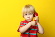 Portrait of little boy with handset on yellow background