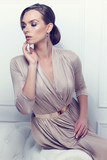 Fashion portrait of beautiful lady in gold evening dress