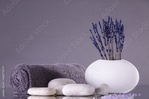 Papiers peints Spa Spa. Lavender flowers stand in a white vase on a gray background. Pebbles and a towel rolled into a roll.