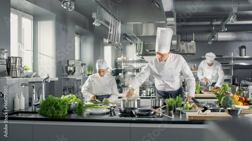 Famous Chef Works in a Big Restaurant Kitchen with His Help. Kitchen is Full of Food, Vegetables and Boiling Dishes. - 166179880