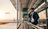 Businessman on airport lounge balcony making phone call - 166187400