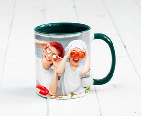 Big green cup with dark green handle and print of a kids cooking something