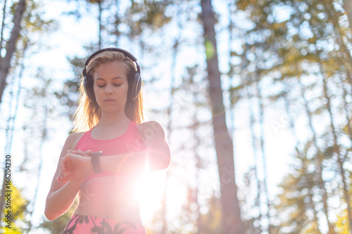 Poster Young attractive sportswoman listening to music wearing headphones and checking her smart watch. Sport, fitness, workout concept