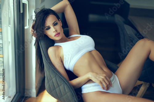 Sexy brunette woman in white underwear posing in comfortable seat Poster
