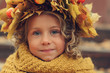 closeup autumn portrait of cute child girl in wreath made of dried leaves and orange knitted snood