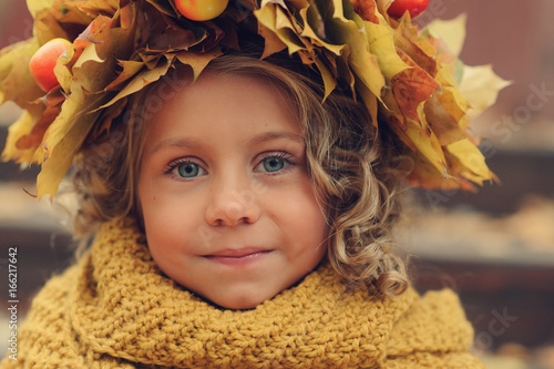 closeup autumn portrait of cute child girl in wreath made of dried leaves and orange knitted snood - 166217642