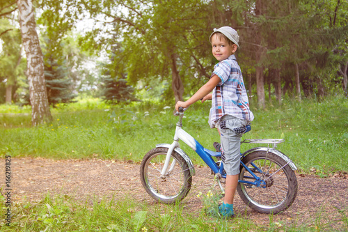 Kid on bike looking at camera and smiling