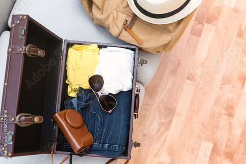 Packing a suitcase and backpack for a trip - 166220616