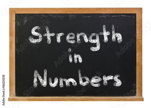 Strength in numbers written in white chalk on a black chalkboard isolated on white