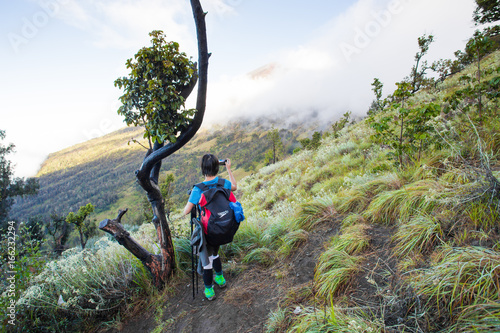 Asian traveling backpacker in volcano mountain Rinjani of Indonesia.
