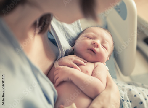 Parenting and new life concept. Mother holding newborn baby boy in her arms.