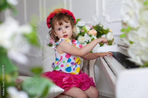 Маленькая девочка в красном венке из цветов играет на пианино Poster