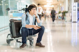 Young Asian man feeling exhausted in airport terminal