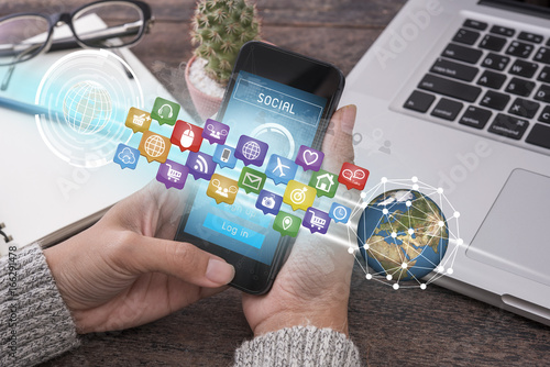 hand holding smart phone with application icons interface and globe networking system. concept technology social network communication.