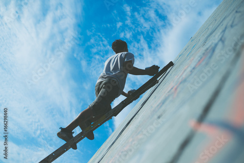 writer at work on a high ladder with spray can