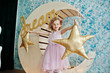 Beautiful little girl in a dress posing next to wooden moon decoration with golden star pillows.