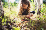 happy child girl picking wild mushrooms on the walk in summer or autumn forest - 166321257
