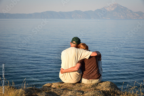Couple in love sitting on the top of the hill in the sunset, hugging and enjoyin Poster