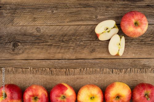 Red apples on the old wooden table. - 166325420