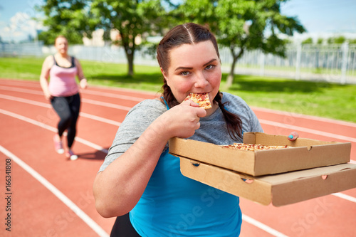 Young fat female with two carton boxes of yummy takeaway pizza eating one during training