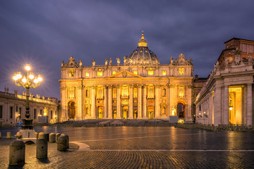 Sunrise over the St. Peters Basilica in Vatican City. Morning at the most famous landmark, empty of people street, cloudy sky.