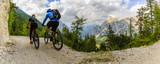 Mountain biking couple with bikes on track, Cortina d'Ampezzo, Dolomites, Italy - 166346828