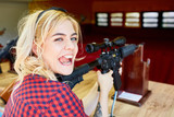 Portrait of cheeky blond girl holding big rifle at shooting stand in amusement park - 166347007