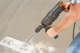 Drill beats concrete with pieces of dust and stone - 166347067