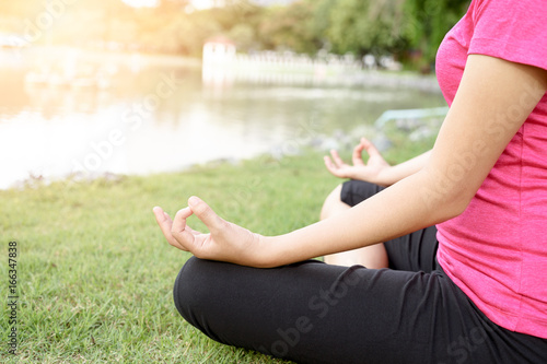 Close up hand with lotus shape - woman do yoga in the park.