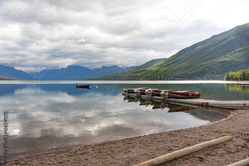 Boats on the Pier with Mountainrange background and mirror-like lake McDonald wi