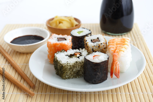 Selection of sushi on bamboo mat with chopsticks, soya sauce and pickled ginger Poster