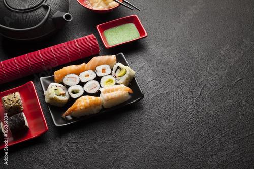 Sushi set and black teapot on black table