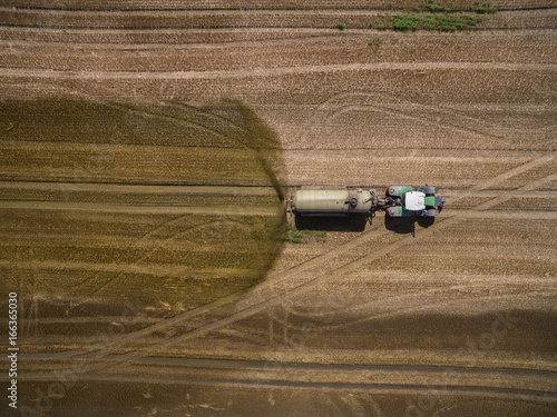 Fotobehang Trekker aerial view of a tractor with a trailer fertilizes a freshly plowed agriculural field with manure in germany