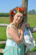 Portrait of the woman of average years with a wreath on the head about a fence