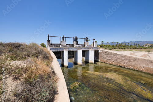ancient open sluices in waterway river, next to Gurugu Beach in Castellon, Valencia, Spain, Europe. Blue clear sky