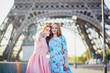 Two friends taking selfie near Eiffel tower in Paris, France