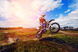 racer on mountain bike participates in motocross race, takes off and jumps on springboard, against the background of the participants. Close-up. concept of extreme rest, sports racing. ray of light - 166373414