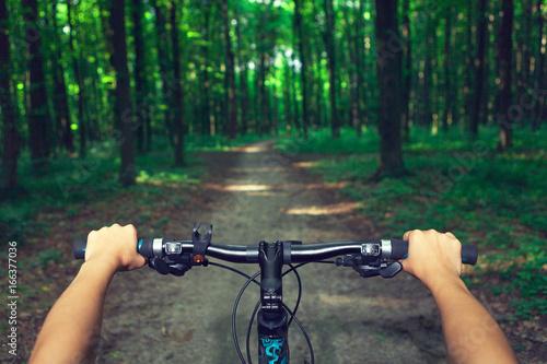 Rower górski w dół wzgórza malejącej szybko na rowerze. Widok z oczu rowerzystów.