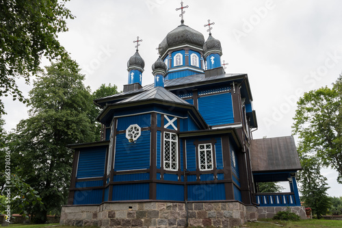 Building of the blue wooden antique orthodox church of Care of the Mother of God Poster