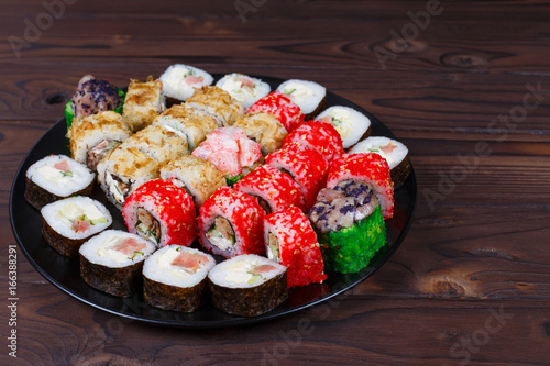 Colorful set of japanese sushi maki rolls with salmon, tuna and avocado served on round plate