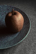 Granite-like sculpture of apple on a plate - 166398683