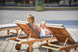 woman looking at her smartphone in deck chair outside in summertime