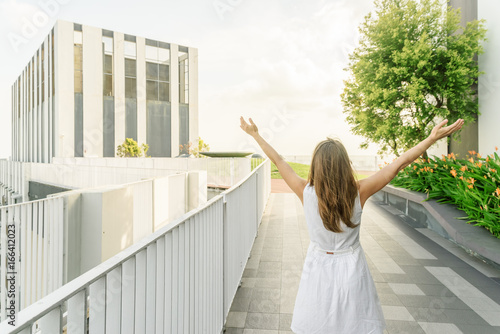Girl with raised arms to the sky enjoying summer time