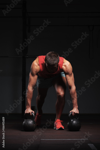 Muscular athletic man exercising in gym