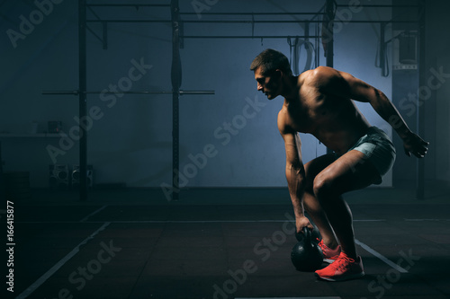 Young man with naked torso working out in gym