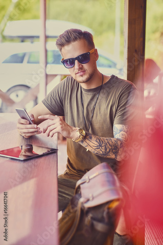 Stylish male with tattooed arms using smartphone indoor. © Fxquadro