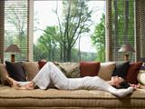 Woman sleeping on sofa in living room - 166462847